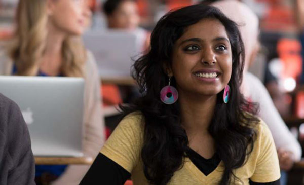 A student sitting in a lecture hall smiling.